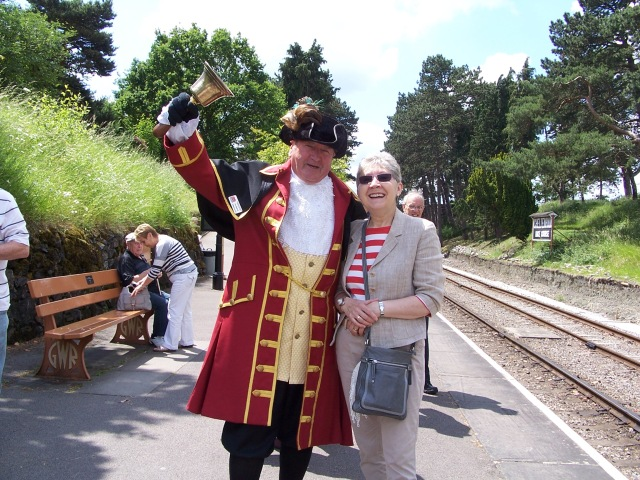 Pam with the Town Crier at Cheltenham Racecourse Station.