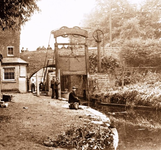 One of the Guillotine Lock Gates at Lifford Lane Bridge on the Stratford-upon-Avon Canal. The building to the left is the toll collector's office. The lock gates were located about 350 yards from the end of the canal where it joins the Worcester Canal. This first section of the canal was completed to Lapworth by 1802. Since the nationalisation of the canals in 1948, water loss from one canal to another is less of an issue, so the gates are no longer in use and are both left open. The last recorded use of the gates was 1959. This photo shows how fascinated the English are by canals – there are spectators in abundance on the bridge and the canal side even in these early days. Or are they supposed to be working?