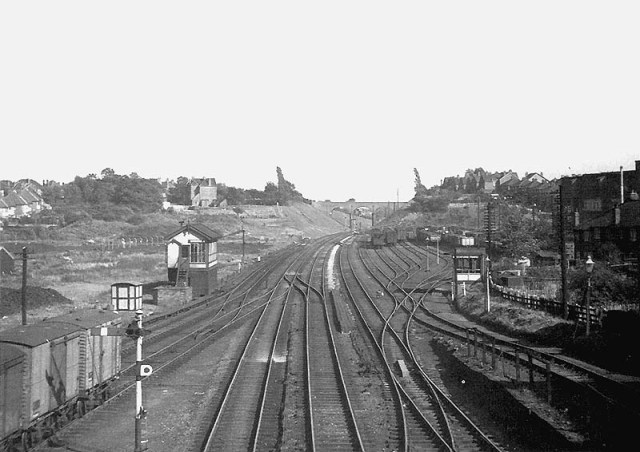 "Panoramic view of the approaches on the Coventry side of Stechford station with the down sidings on the right as seen on 7th September 1957. Amateur photographer Dennis Norton is standing on Station Road bridge with Hill House bridge in the distance. Stechford No 1 Signal Box is seen on the left. On the right is the ""hump"" used to 'fly shunt' wagons in to the down sidings. [Photo by DJ Norton]"